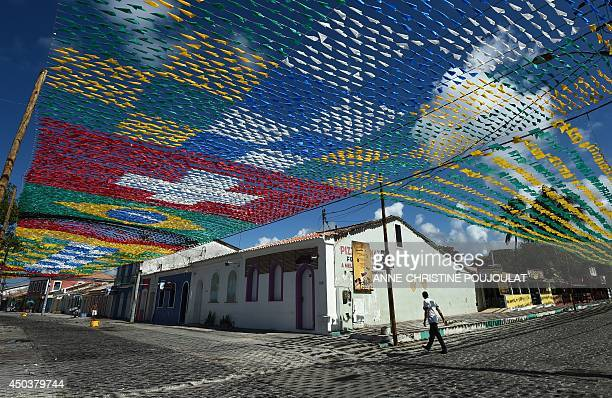 A pedestrian walks along a street under a canopy of national flags of countries participating in the forthcoming 2014 FIFA World Cup in Porto Seguro...