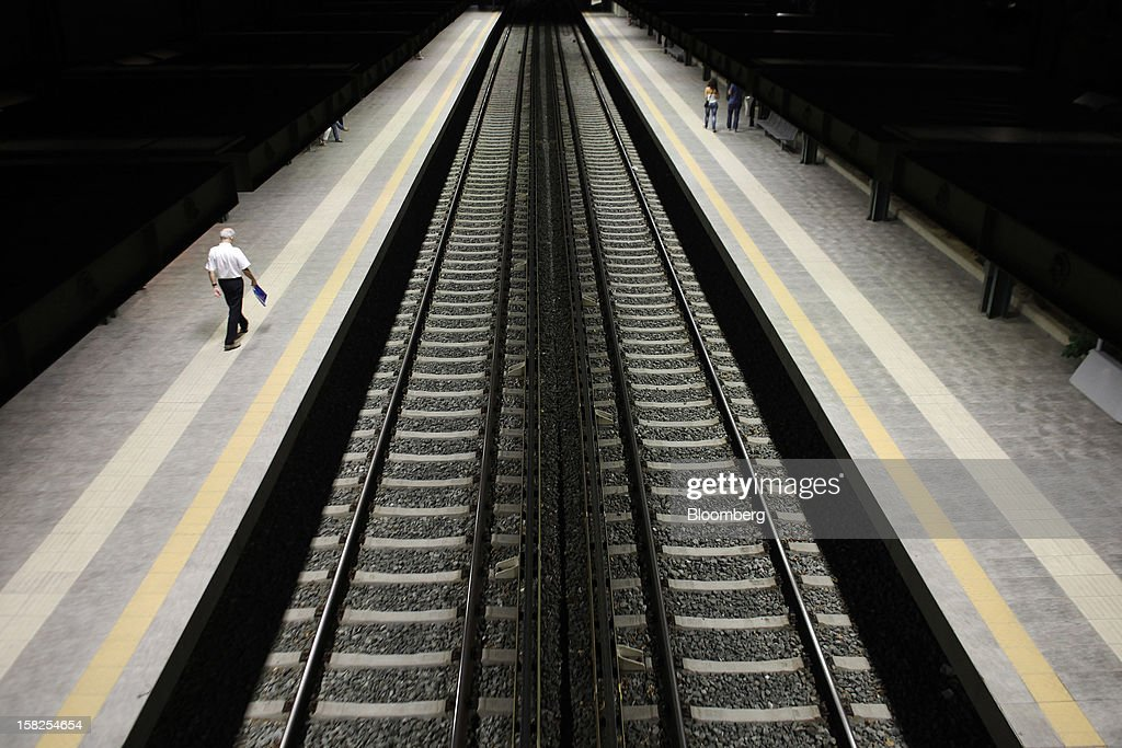 'BEST PHOTOS OF 2012' (): A pedestrian walks along an illuminated train platform past electric rail lines at Thissio in Athens, Greece, on Monday, Aug. 13, 2012. The Greek government plans to make it easier for investors to buy stakes of more than 20 percent in state-controlled companies that are considered strategically important, such as Public Power Corp. SA, Imerisia reported, without citing anyone. Photographer: Angelos Tzortzinis/Bloomberg via Getty Images