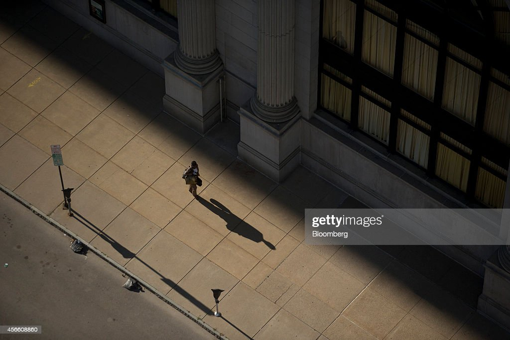 A pedestrian walks along Genesee Street in Buffalo New York US on Wednesday Sept 24 2014 The Federal Reserve Bank of New York's empire state...