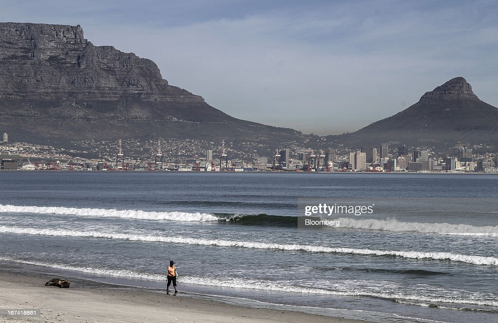 A pedestrian walks along the beach backdropped by the commercial harbour and city centre in Cape Town, South Africa, on Wednesday, April 24, 2013. South Africa's gross domestic product is forecast to expand 2.6 percent this year, compared with 2.5 percent in 2012, according to the country's central bank. Photographer: Nadine Hutton/Bloomberg via Getty Images