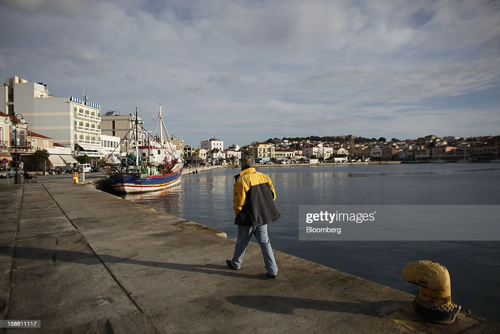A pedestrian walks along the dockside at Mytilene harbor on the island of Lesbos, Greece, on Saturday, Dec. 8, 2012. In recent months, Lesbos has become a hot spot for migrants as Greece struggles to cope with waves of refugees from Middle Eastern conflict even as it reels from economic crisis at home. Photographer: Kostas Tsironis/Bloomberg via Getty Images