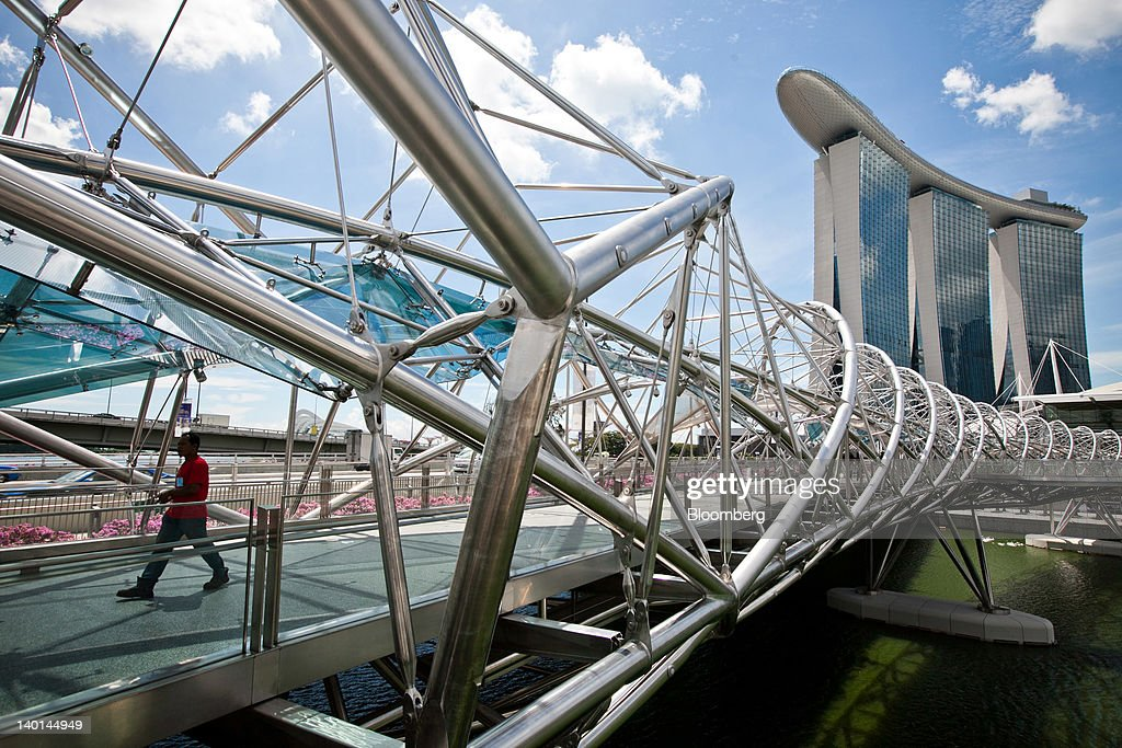 A pedestrian walks along the Helix Bridge as Marina Bay Sands stands in the background in Singapore, on Tuesday, Feb. 28, 2012. The number of visitors to the island rose to a record 13.2 million in 2011 as casino-resorts run by Genting Singapore Plc and Las Vegas Sands Corp. lured tourists. Photographer: Sam Kang Li/Bloomberg via Getty Images