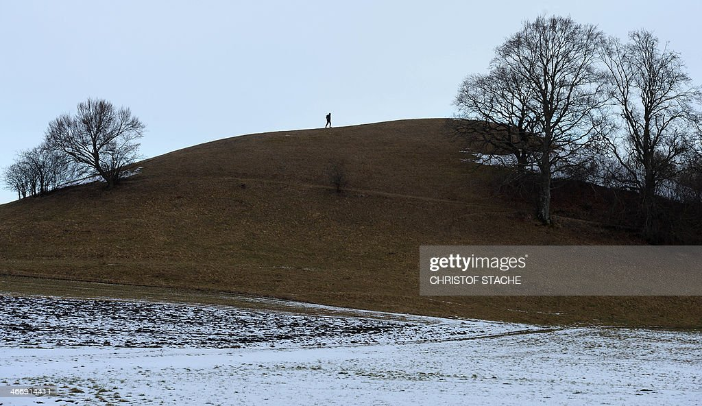 A pedestrian walks at a small hill without snow near the village Andechs, southern Germany, during winter weather and temperatures by the freezing point on February 5, 2014. Meteorologists forecast changeable weather during the week.