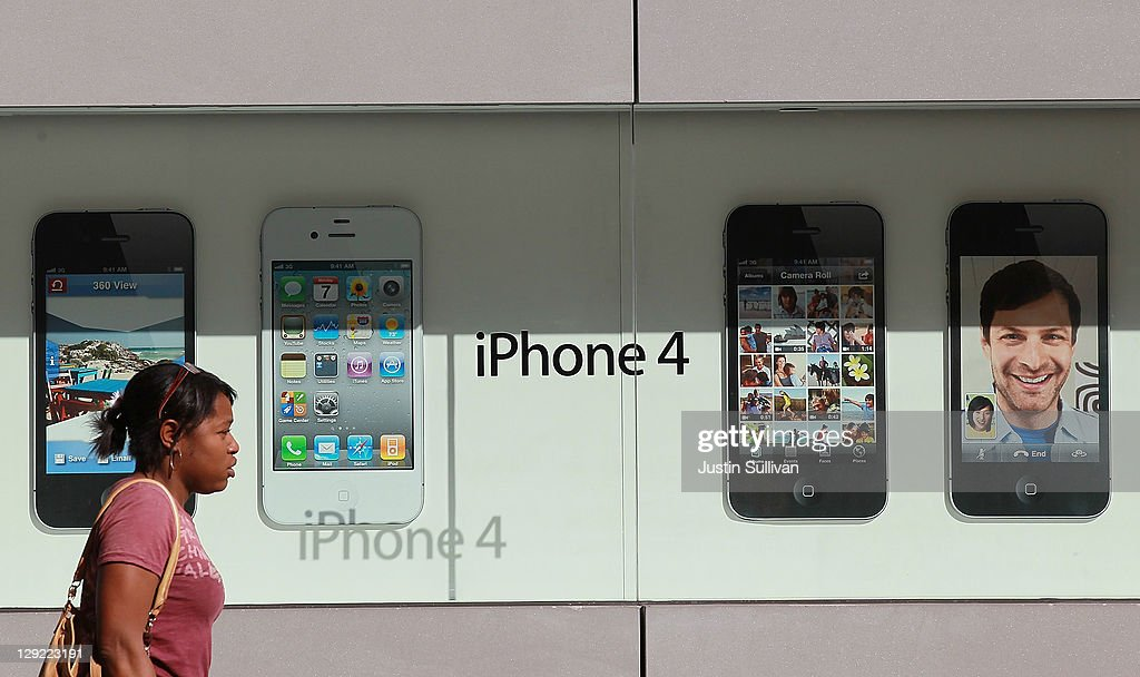 A pedestrian walks by a display of the new Apple iPhone 4Gs at an Apple Store on October 14, 2011 in San Francisco, United States. The new iPhone 4Gs went on sale today and features a faster dual-core A5 chip, an 8MP camera that shoots 1080p HD video, and a voice assistant program.
