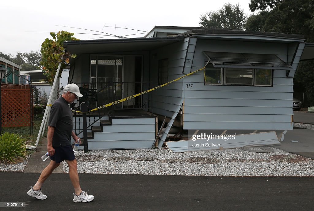 A pedestrian walks by a mobile home that shifted off of its foundation at a mobile home park following a reported 6.0 earthquake on August 24, 2014 in Napa, California. A 6.0 earthquake rocked the San Francisco Bay Area shortly after 3:00 am on Sunday morning causing damage to buildings and sending at least 70 people to a hospital with non-life threatening injuries.