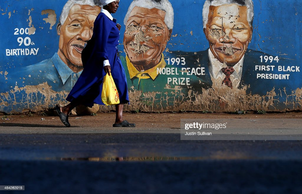 A pedestrian walks by a mural of Nelson Mandela on December 8, 2013 in Soweto, South Africa. Mandela, also known as Madiba, passed away on the evening of December 5th, 2013 at his home in Houghton at the age of 95. Mandela became South Africa's first black president in 1994 after spending 27 years in jail for his activism against apartheid in a racially-divided South Africa.