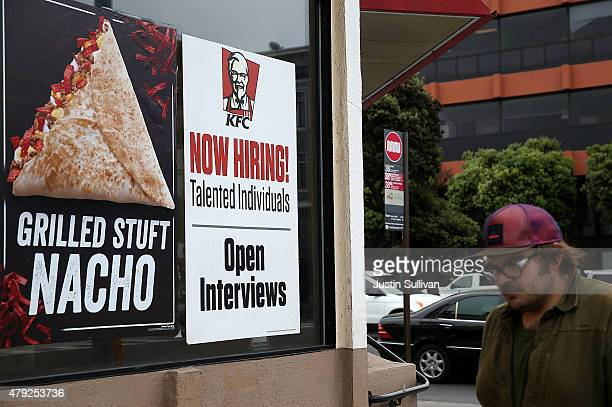 A pedestrian walks by a 'now hiring' sign at a KFC restaurant on July 2 2015 in San Francisco California According to a report by the US Labor...