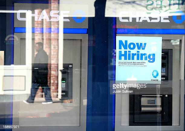 A pedestrian walks by a 'now hiring' sign that is posted in the window of a Chase bank branch on January 4 2013 in San Rafael California According to...