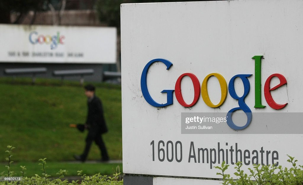 A pedestrian walks by a sign that is posted outside of the Google headquarters January 21, 2010 in Mountain View, California. Google will report fouth quarter earnings today.