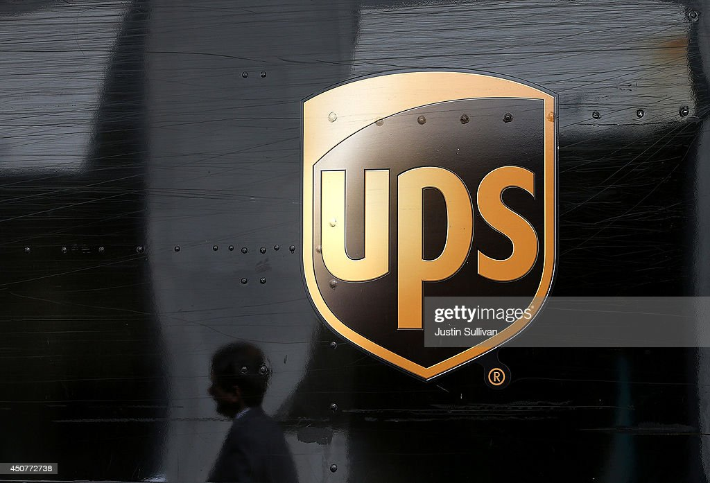 A pedestrian walks by a United Parcel Service (UPS) truck on June 17 & Fotos e imágenes de UPS To Factor Box Size Into New Pricing Method ... Aboutintivar.Com