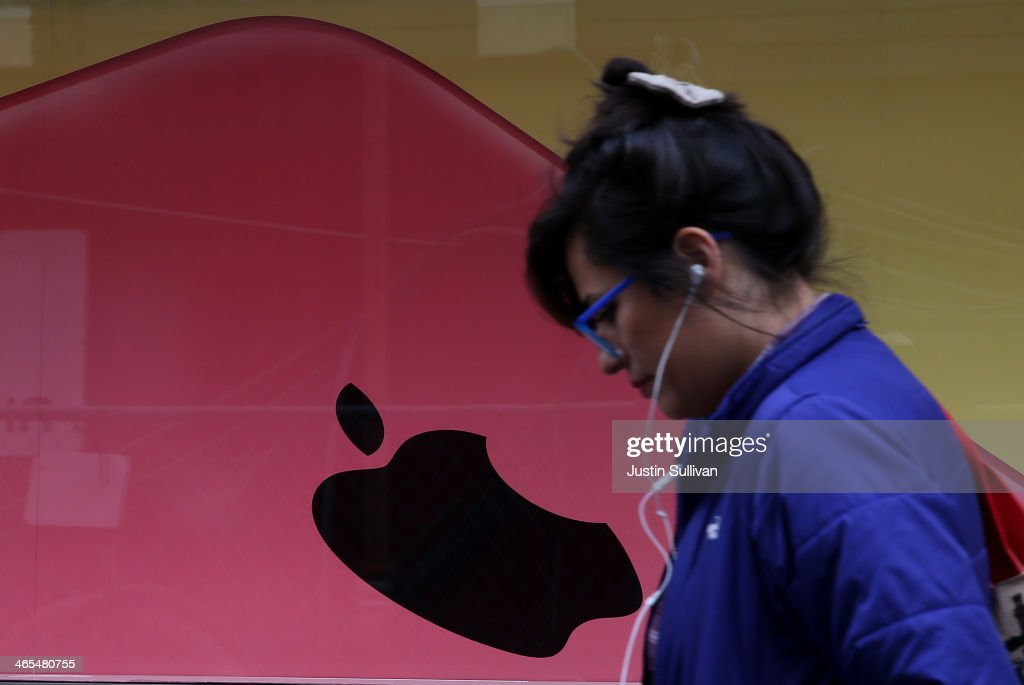 A pedestrian walks by a window display at an Apple Store on January 27, 2014 in San Francisco, California. Apple will report quarterly earnings today after the closing bell.