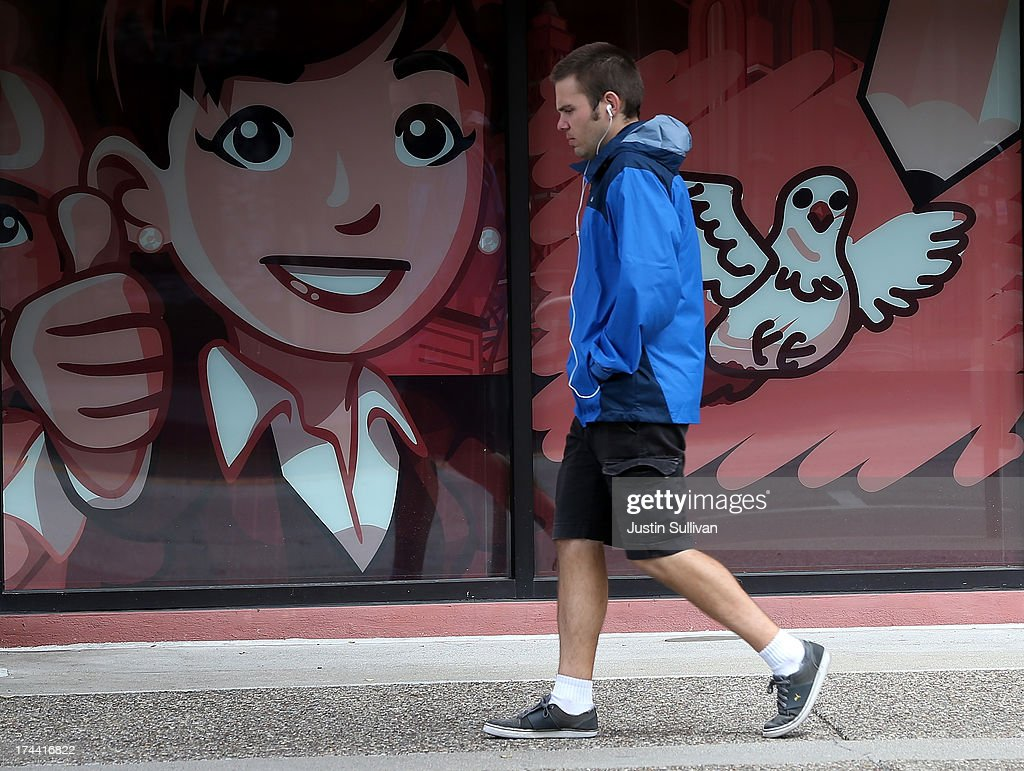 A pedestrian walks by a window display at the Zynga headquarters on July 25, 2013 in San Francisco, California. Online game maker Zynga will report second quarter earnings after the market close.