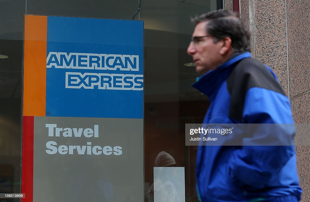 A pedestrian walks by an American Express Travel Services office on January 11, 2013 in San Francisco, California. American Express Co. is planning to cut 5,400 jobs, or 8.5% of its workforce. Most of the cuts will fall on its struggling travel division that has been unable to keep up with low cost internet travel sites.