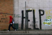 A pedestrian walks by graffiti on a downtown street November 20 2008 in Detroit Michigan An estimated one in three Detroiters lives in poverty making...