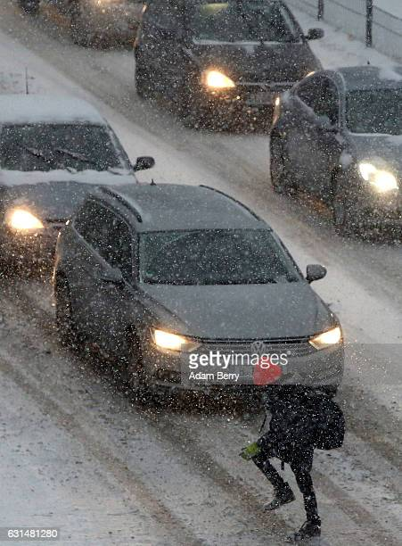 A pedestrian walks carefully across a street to avoid slipping on ice during heavy snowfall on January 11 2017 in Berlin Germany Cold weather has...