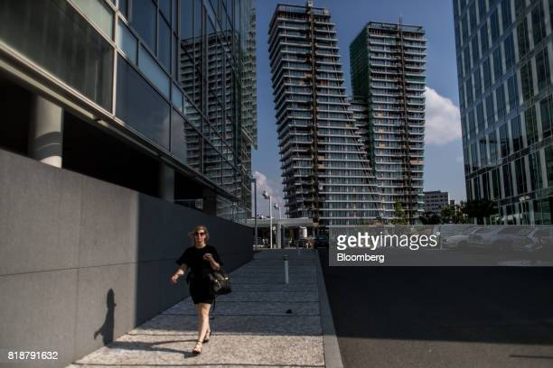 A pedestrian walks down the street as the 'V Tower' luxury residential apartment block stands beyond in the Pankrac district of Prague Czech Republic...