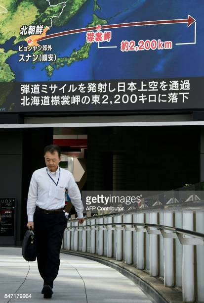 A pedestrian walks in front of a large video screen in Tokyo broadcasting a news report about North Korea's latest missile test that passed over...