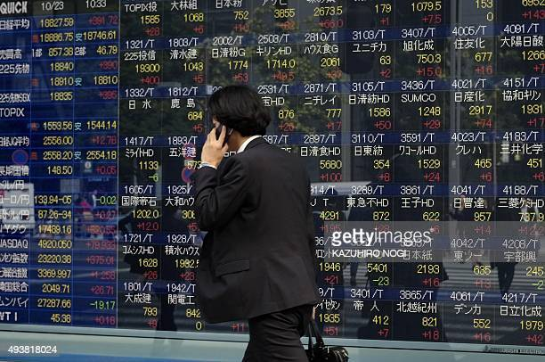 A pedestrian walks in front of a share prices board showing the numbers on the Nikkei 225 at the Tokyo Stock Exchange in Tokyo on October 23 2015...