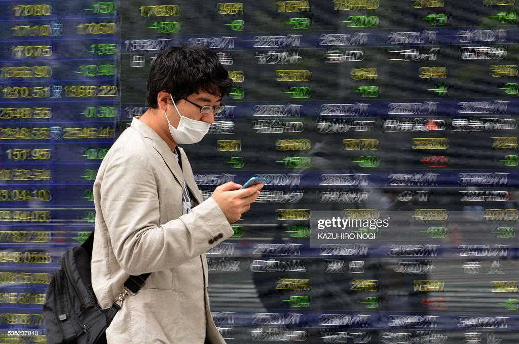A pedestrian walks in front of an electronic stock quotation board displayed at a securities company in Tokyo on June 1, 2016. Tokyo stocks opened lower June 1 as profit-taking set in after five straight positive sessions, following a weak lead from Wall Street. / AFP / KAZUHIRO