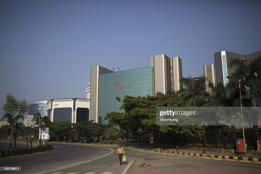 A pedestrian walks in front of the Wockhardt Ltd. headquarters in the Bandra Kurla Complex in Mumbai, India, on Tuesday, Nov. 6, 2012. Reserve Bank of India Governor Duvvuri Subbarao lowered the RBI's forecast for India's gross domestic product growth in the year through March to 5.8 percent, the slowest in almost a decade, from 6.5 percent. Photographer: Brent Lewin/Bloomberg via Getty Images