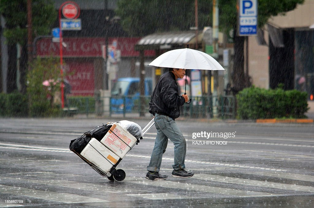 A pedestrian walks in heavy rain in Tokyo on October 26, 2013. People on a storm-battered island in Japan took shelter October 25, as another typhoon -- one of two looming in the Pacific -- looked set to sideswipe the coast.