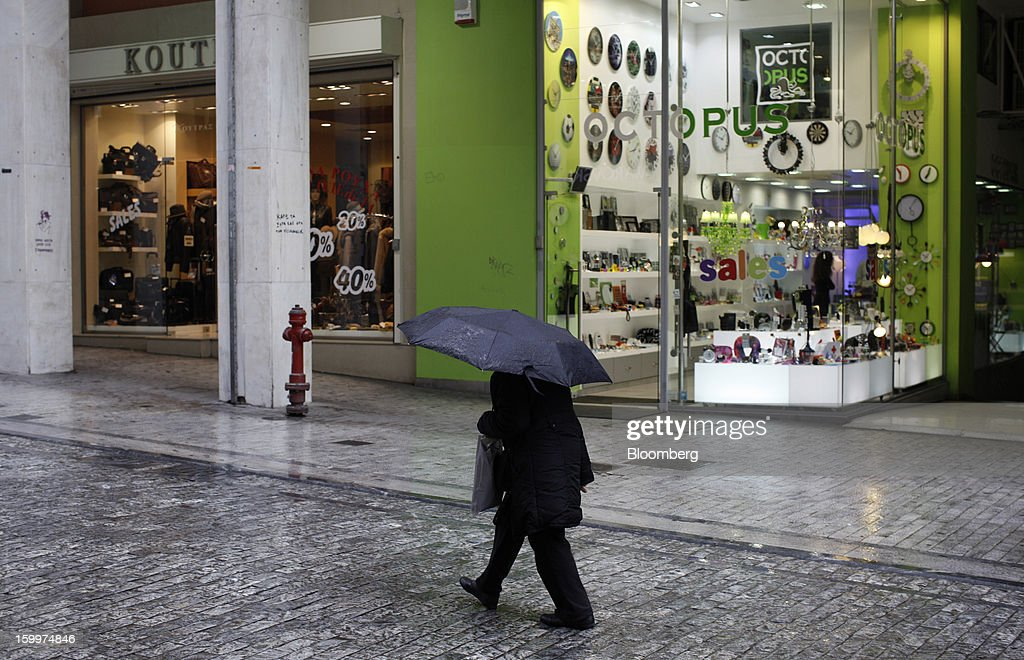 A pedestrian walks in the rain beneath an umbrella past retail stores in Athens, Greece, on Thursday, Jan. 24, 2013. Greece's government has implemented budget cuts and economic reforms to tame a fiscal deficit that has led to bailouts from the European Union and the International Monetary Fund. Photographer: Kostas Tsironis/Bloomberg via Getty Images