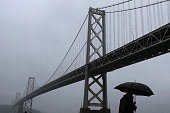 A pedestrian walks in the rain next to the San FranciscoOakland Bay Bridge on December 11 2014 in San Francisco California The San Francisco Bay Area...