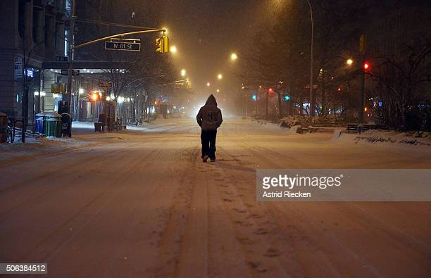 A pedestrian walks in the snow on Broadway at West 81st street on January 23 2016 in New York City A major Nor'easter is hitting much of the East...