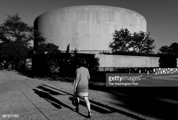 A pedestrian walks near the Hirshhorn Museum which is one of several buildings of brutalism architecture in Washington DC April 28 2017 Named after...