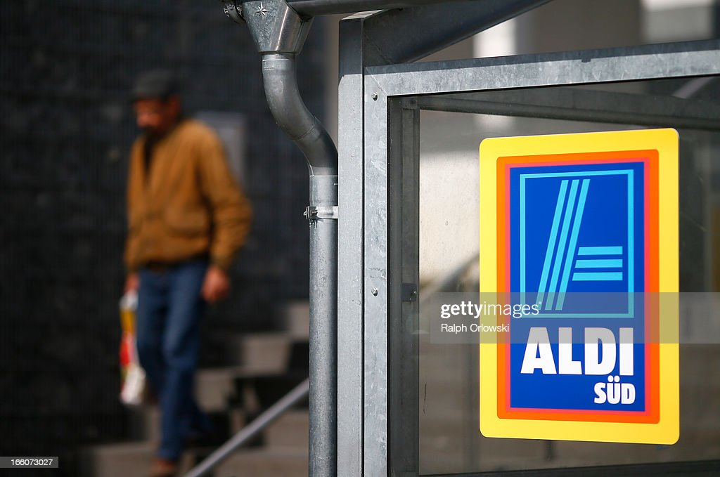 A pedestrian walks next to an Aldi logo at an Aldi store on April 8, 2013 in Ruesselsheim near Frankfurt, Germany. Aldi, which today is among the world's most successful discount grocery store chains, will soon mark its 100th anniversary and traces its history back to Karl Albrecht, who began selling baked goods in Essen on April 10, 1913 and founded the Aldi name by shortening the phrase Albrecht Discount. His sons Karl Jr. and Theo expanded the chain dramatically, creating 300 stores by 1960 divided between northern and southern Germany, with Aldi Nord and Aldi Sued, respectively. Today the two chains have approximately 4,300 stores nationwide and have also expanded into other countries across Europe and the USA. Aldi Nord operates in the USA under the name Trader Joe's.