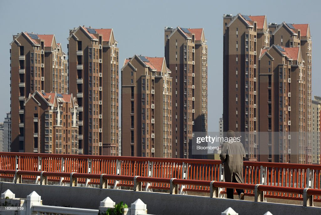 A pedestrian walks on a bridge in front of residential buildings at the Sino-Singapore Tianjin Eco-city in Tianjin, China, on Wednesday, March 13, 2013. China's money-market rate rose to a one-week high after central bank Governor Zhou Xiaochuan said yesterday the nation should be on 'high alert' over inflation. Photographer: Tomohiro Ohsumi/Bloomberg via Getty Images