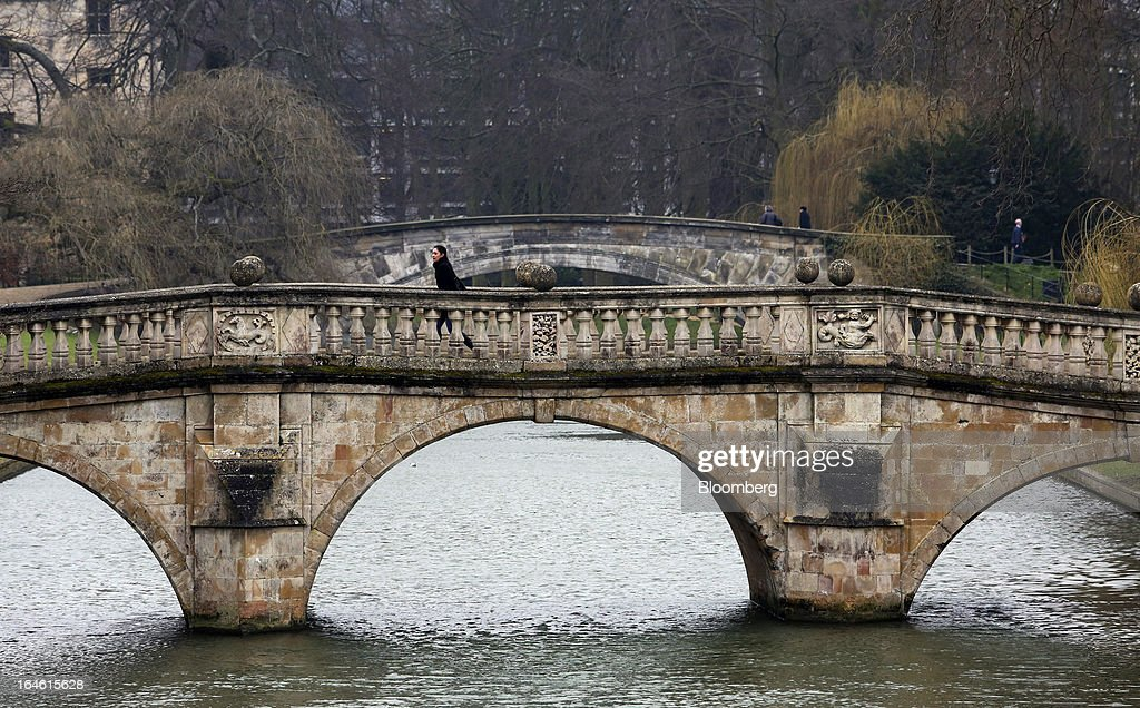 A pedestrian walks on a bridge spanning the River Cam near Trinity College, part of the University of Cambridge, in Cambridge, U.K., on Friday, March 22, 2013. In 2011, the U.K.'s government unveiled a plan to reduce state spending on higher education and shift more of the costs to students through tuition increases and a loan program. Photographer: Chris Ratcliffe/Bloomberg via Getty Images