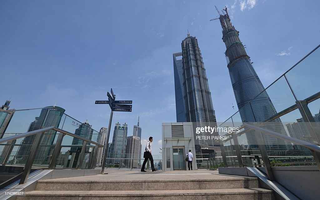 A pedestrian walks on an overpass in Pudong, Shanghai's financial district, on July 23, 2013. China's economic growth must not slip below the 'bottom line' of seven percent, Premier Li Keqiang was quoted as saying by a state-backed newspaper on July 23, with the target being necessary to ensure China achieved its goal of doubling its gross domestic product between 2010 and 2020. AFP PHOTO/Peter PARKS
