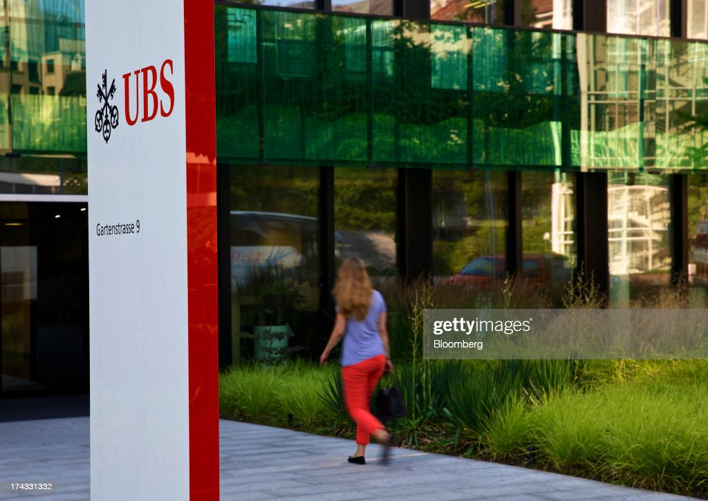 A pedestrian walks outside the offices of UBS AG as the bank's logo is displayed in Basel, Switzerland, on Tuesday, July 23, 2013. Europe's biggest banks, which more than doubled their highest-quality capital to $1 trillion since 2007 to meet tougher rules, may have further to go as regulators scrutinize how lenders judge the riskiness of their assets. Photographer: Gianluca Colla/Bloomberg via Getty Images