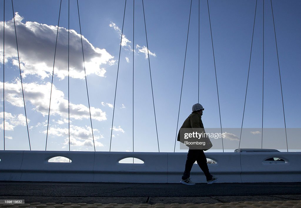 A pedestrian walks over a bridge in Toyota City, Aichi Prefecture, Japan, on Friday, Jan. 18, 2013. Toyota Motor Corp., poised to regain its title as the world's biggest carmaker this year, said last month its vehicle sales may rise 2 percent next year to a record, led by demand from overseas markets. Photographer: Tomohiro Ohsumi/Bloomberg via Getty Images