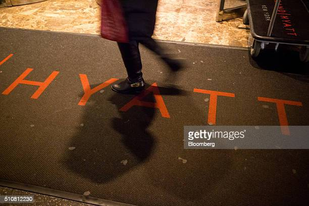 A pedestrian walks over a floor mat displaying Hyatt Hotels Corp's logo outside of the Grand Hyatt at 109 East 42nd street in New York US on Tuesday...