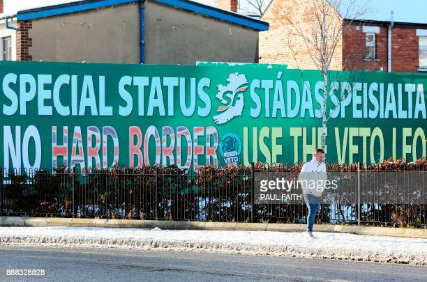 A pedestrian walks past a billboard in west Belfast on December 8 2017 erected by Republican Party Sinn Fein calling for a special status for...