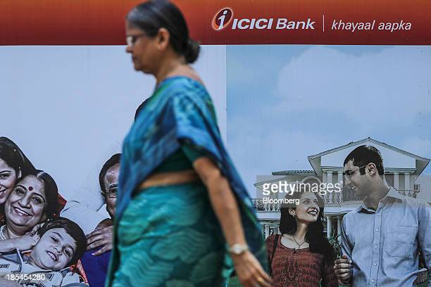 A pedestrian walks past a branch of ICICI Bank Ltd in Mumbai India on Saturday Oct 19 2013 ICICI Bank is scheduled to release quarterly earnings on...