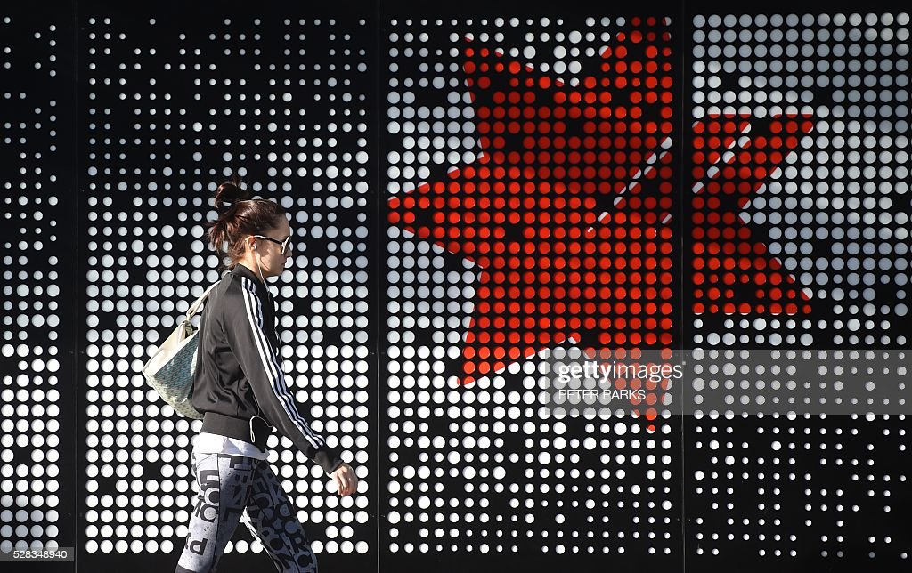 A pedestrian walks past a branch of the National Australia Bank (NAB) in Sydney on May 5, 2016. National Australia Bank earnings jumped as bad debt charges fell but it booked a hefty 1.74 billion AUD (1.29 billion USD) interim net loss on May 5 from spinning off troubled British asset Clydesdale. / AFP / PETER