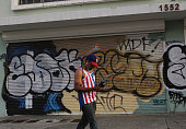 A pedestrian walks past a building tagged with graffiti a day after Puerto Rican Governor Alejandro Garcia Padilla gave a televised speech regarding...