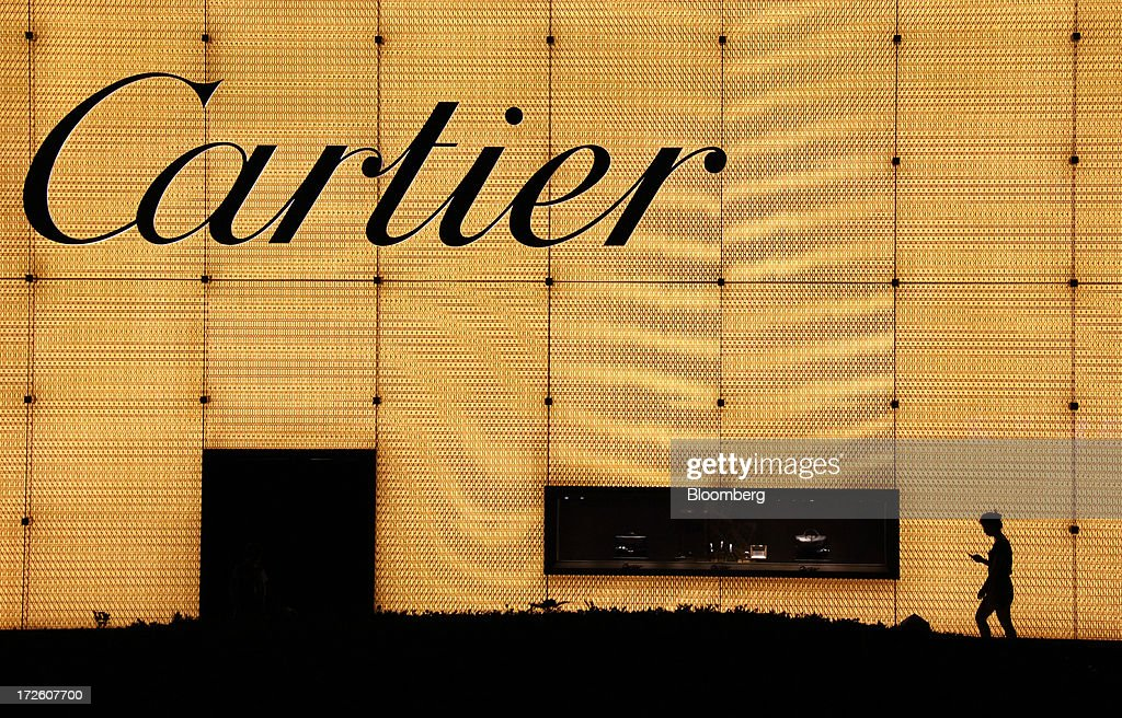 A pedestrian walks past a Cartier store, operated by Cie. Financiere Richemont SA, as it stands illuminated at night in Shanghai, China, on Tuesday, July 2, 2013. Banks including Goldman Sachs Group Inc. have pared their growth projections for China this year to 7.4 percent, below the government's 7.5 percent goal disclosed at the March conference at which Li Keqiang became premier. Photographer: Tomohiro Ohsumi/Bloomberg via Getty Images