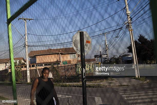 A pedestrian walks past a chain link fence in the Puerto Principe area of the Quilicura district in Santiago Chile on Thursday Nov 10 2016 More than...