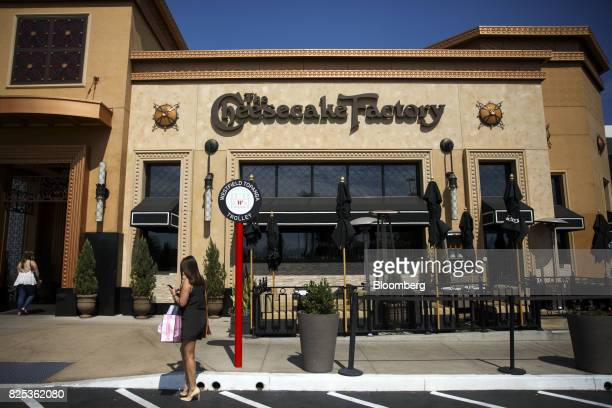 A pedestrian walks past a Cheesecake Factory Inc restaurant in the Canoga Park neighborhood of Los Angeles California US on Tuesday Aug 1 2017 The...
