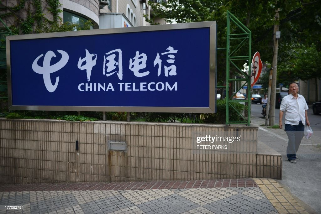 A pedestrian walks past a China Telecom sign on a street in Shanghai on August 21, 2013. China Telecom said on August 21 its net profit in the first six months of the year rose 15.9 percent year-on-year, citing growth in its 3G mobile operation. AFP PHOTO / Peter PARKS