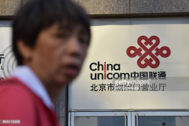 A pedestrian walks past a China Unicom sign in Beijing on August 17 2017 A plan under which big Chinese companies led by Tencent and Alibaba would...