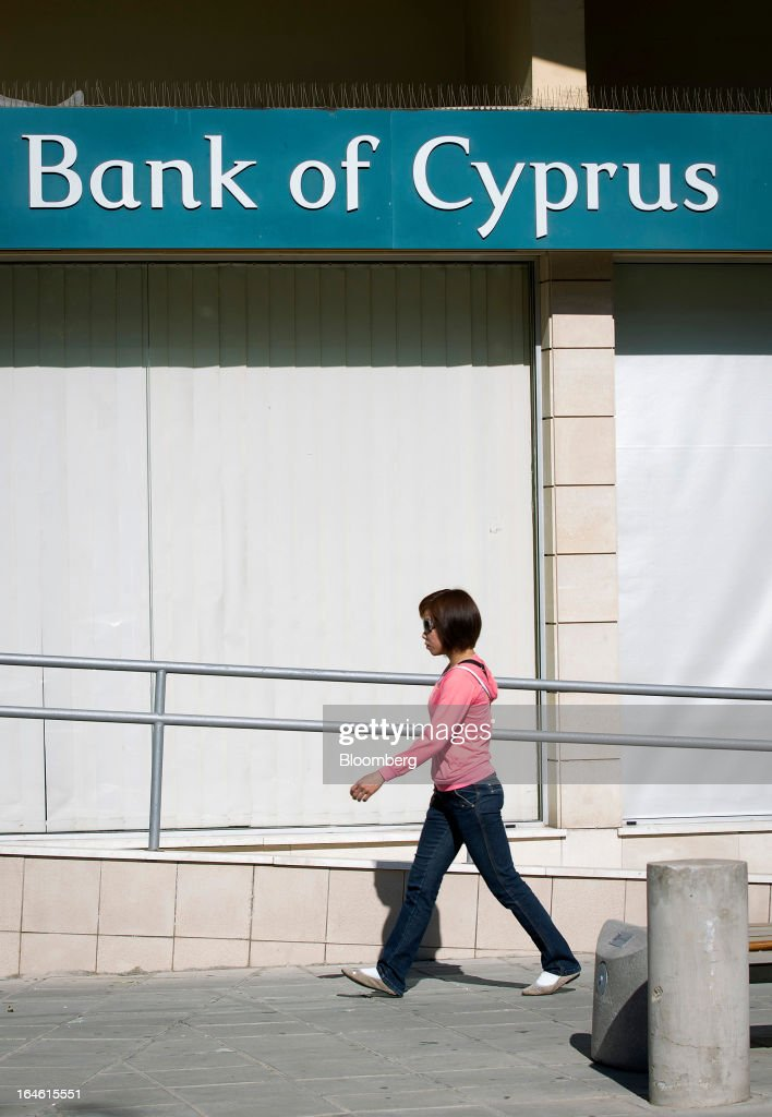 A pedestrian walks past a closed Bank of Cyprus Plc branch in Nicosia, Cyprus, on Monday, March 25, 2013. Cyprus dodged a disorderly default and unprecedented exit from the euro by bowing to demands from creditors to shrink its banking system in exchange for 10 billion euros ($13 billion) of aid. Photographer: Simon Dawson/Bloomberg via Getty Images