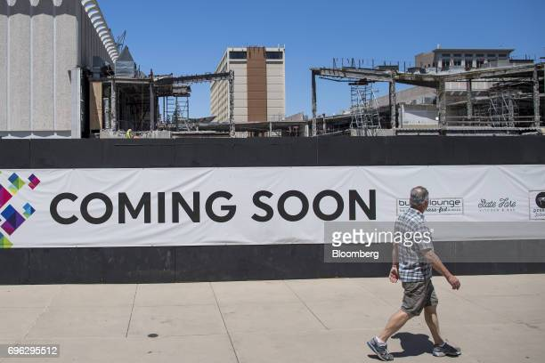 A pedestrian walks past a 'Coming Soon' sign displayed outside of a building under construction in Sacramento California US on Tuesday June 6 2017 As...