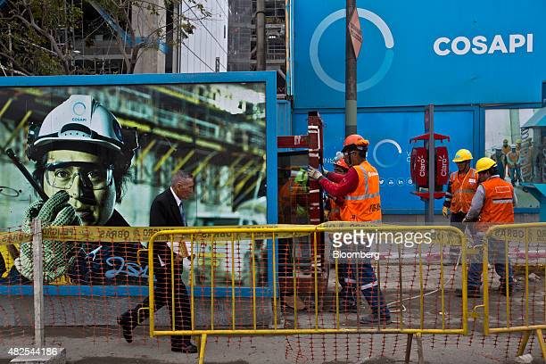 A pedestrian walks past a Cosapi SA banner hanging at the construction site of the Banco de la Nacion state bank headquarters building in the San...
