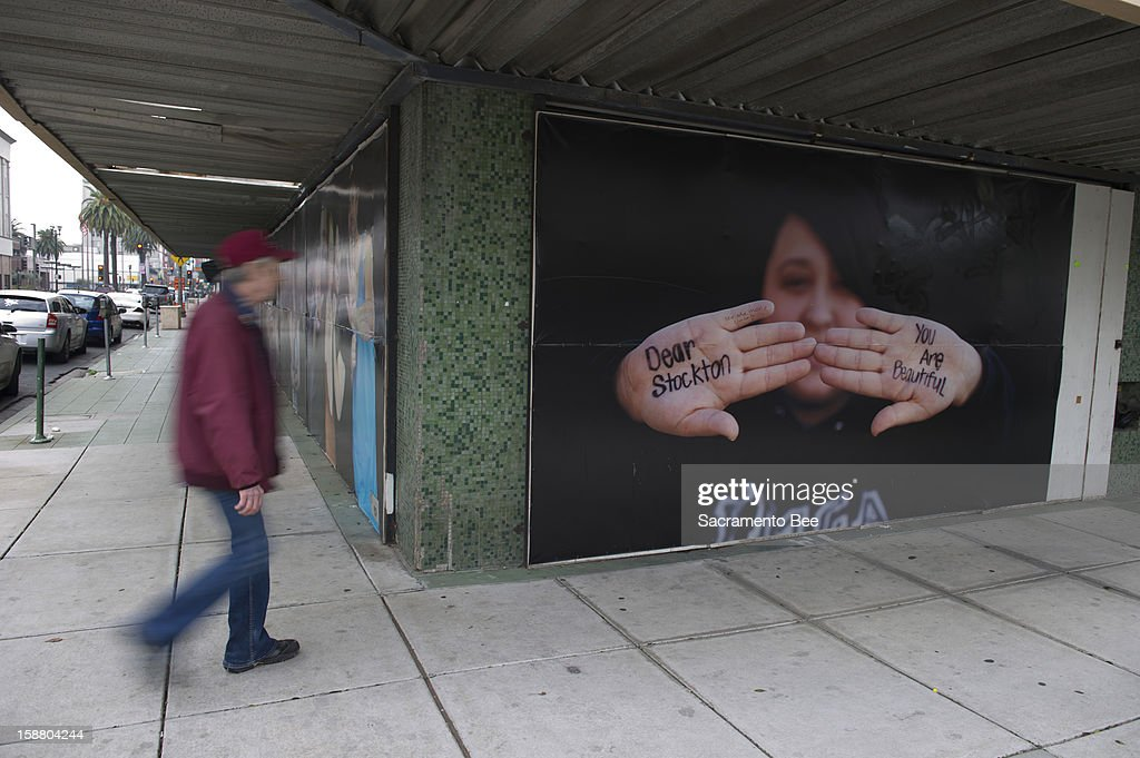 A pedestrian walks past a Dear Stockton photo in downtown Stockton, California, on December 11, 2012. 'Dear Stockton' is an ongoing photography project designed to have people in the community write positive messages to the city.