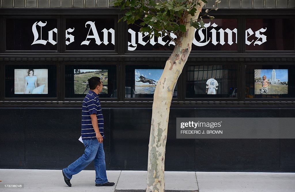 A pedestrian walks past a display of photographs at the Los Angeles Times Building in downtown Los Angeles, California on July 10, 2013. The Tribune Company, a group which owns 23 television stations, announced plans Wednesday to spin off its newspaper division, which includes the Los Angeles Times and Chicago Tribune, separating the struggling unit from its growing television station holdings. Tribune Company last week announced a $2.7 billion deal to buy 19 more local television stations and has said splitting into two distinct companies would give each 'greater financial and operational focus.' AFP PHOTO/Frederic J. BROWN